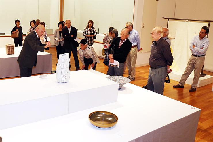 来場者に作品解説する寺田さん(手前左)=高岡市美術館