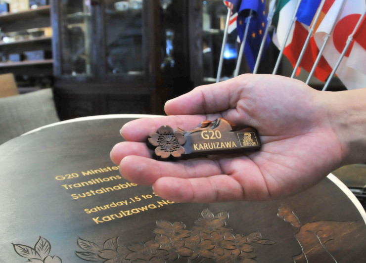 閣僚らが胸に着ける予定の軽井沢彫のバッジ。会場で出席者を迎えるウエルカムボードにも軽井沢彫をあしらった