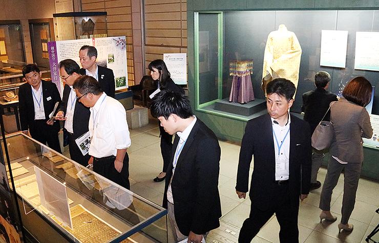 令和の典拠となった万葉集の複製などに見入る参加者=高岡市万葉歴史館