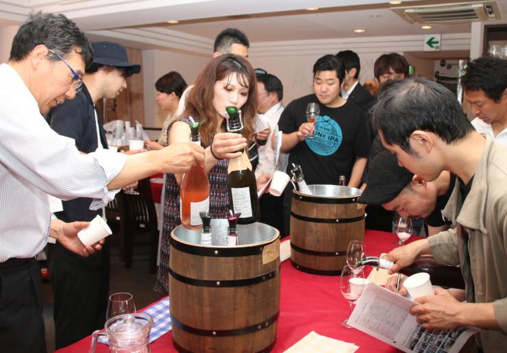 さまざまな県産ワインを試飲する参加者たち