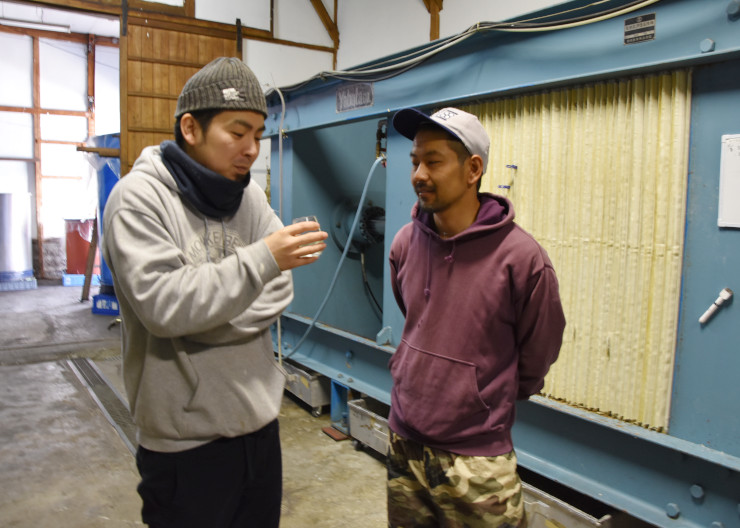 搾りたての日本酒を試飲する飯田さん(左)と、酒米を育てた田野口さん