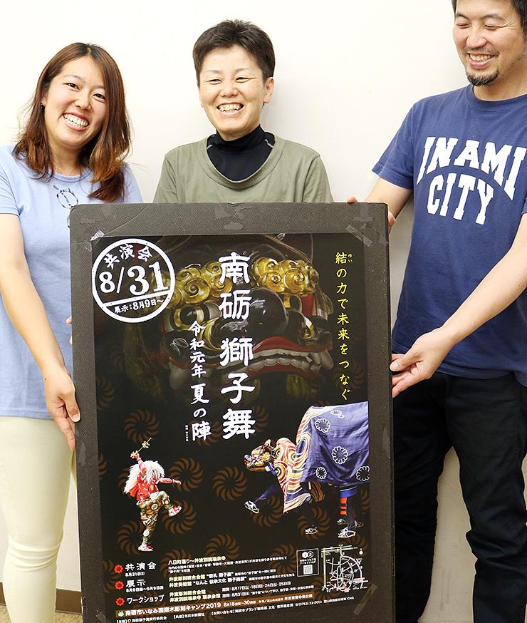 ポスターを持ち、笑顔を見せる実行委員会メンバー