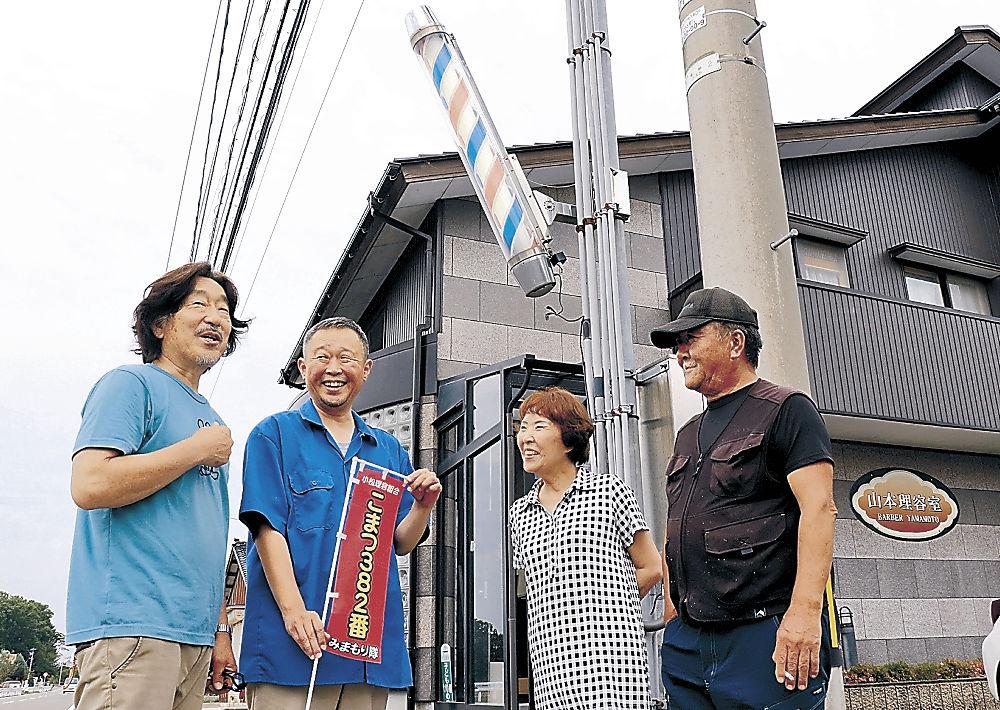 旗を持ち、理容室の前で住民と談笑する山本地区部長(左から2人目)=小松市木場町