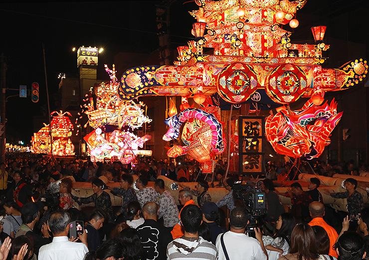 大勢の見物客の前で威勢良く引き回される夜高行燈=砺波市本町