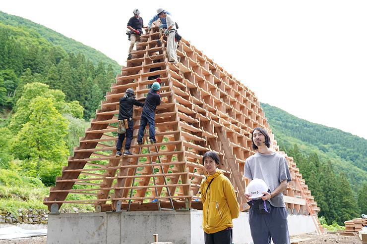 建設中の「まれびとの家」の前に立つ黒部さん(右)と秋吉社長