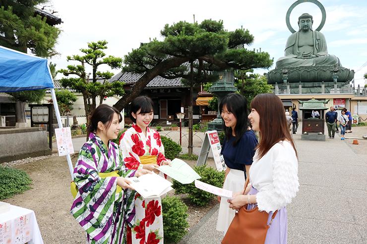 大仏寺を訪れた人にたかおか御朱印帳を紹介する梅原さん(左)と大谷さん(左から2人目)