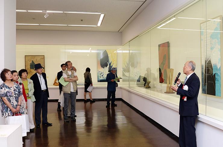 来場者に作品を解説する前川会長(右)=県民会館美術館