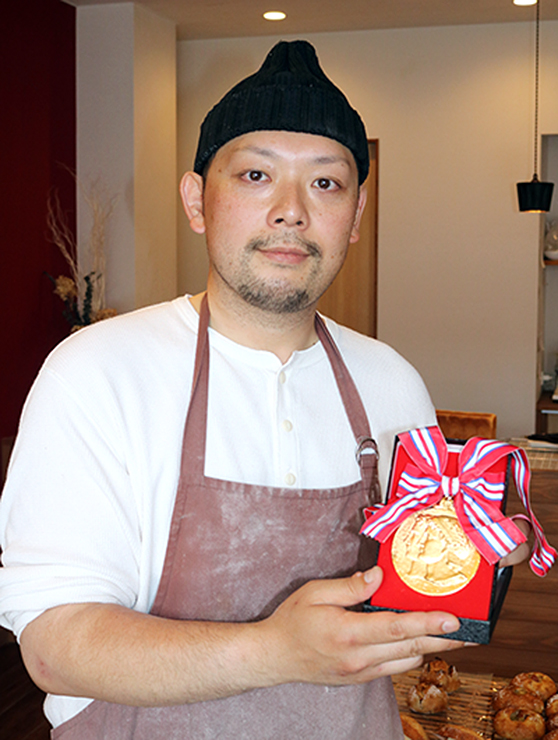 最高賞の金メダルを手にする小嶋さん=ブーランジェリー グラン・オム