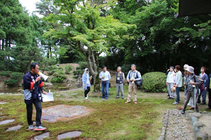 地元住民のガイドで旧家の庭園をめぐる参加者=新発田市米倉