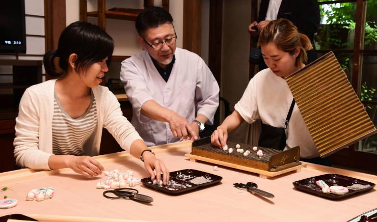 手まり型のあめの作り方を参加者に教える太田さん(中央)