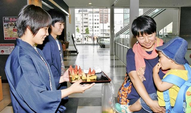 金福すいかと銀福すいかを試食する親子連れ=6月18日、福井県福井市のハピリン内「福福館」