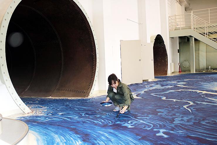 導水管から勢いよく流れ出る水を床面に描く平井さん