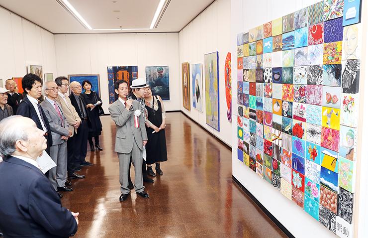 谷内委員長(中央)の説明を聞きながら、コラボレーション作品を鑑賞する来場者=県民会館