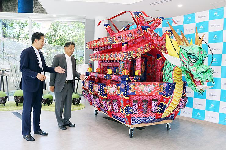 コミュニティースペースに展示された山車を見学する上田社長(左)と萩会長