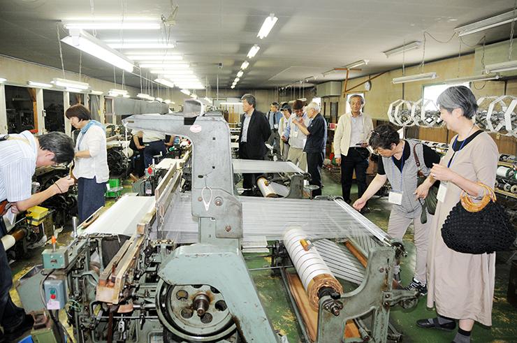 松井機業で機織り機が並ぶ工場を見学する参加者