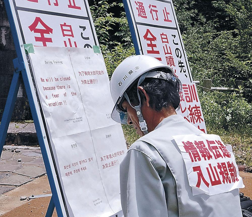 入山規制の看板に貼り付けられた外国語の表示=白山市白峰