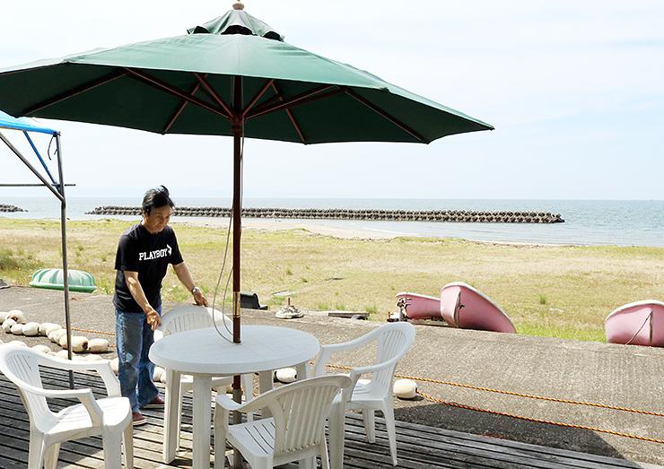 海開きを目前に控え、パラソルやテーブルなどを準備するマリンブルーの林代表