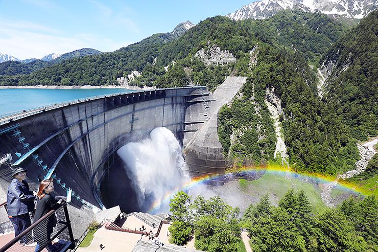 観光放水が始まった黒部ダムと水煙に現れた虹=26日午前10時20分ごろ、立山町芦峅寺