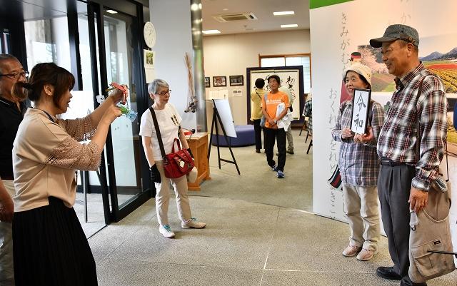 新元号「令和」の書と記念撮影する関西からのツアー客=福井県越前市余川町の「万葉館」