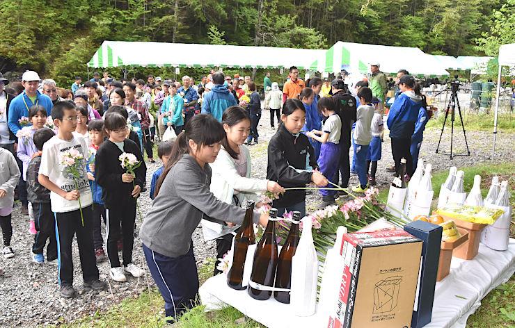 竹沢長衛の功績をたたえ、花を手向ける地元長谷小学校の児童