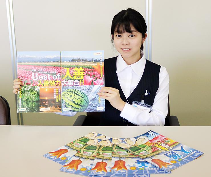繁体字版の観光パンフレットを掲げる入善町職員