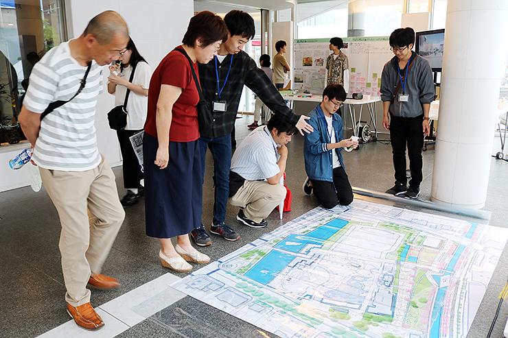 地図を見ながら富山城址公園の利活用を考える学生や来場者=富山市民プラザ