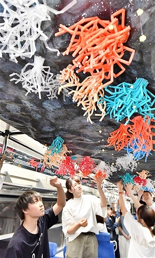 「海の宇宙」をテーマに車両の天井を装飾する学生たち=7月3日、福井県福井市松本上町のえちぜん鉄道車両基地