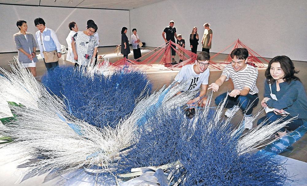 「連」をテーマにした個性豊かな大作を鑑賞する来場者=金沢21世紀美術館