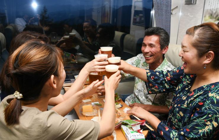テーブルを囲み、ビールで乾杯する乗客