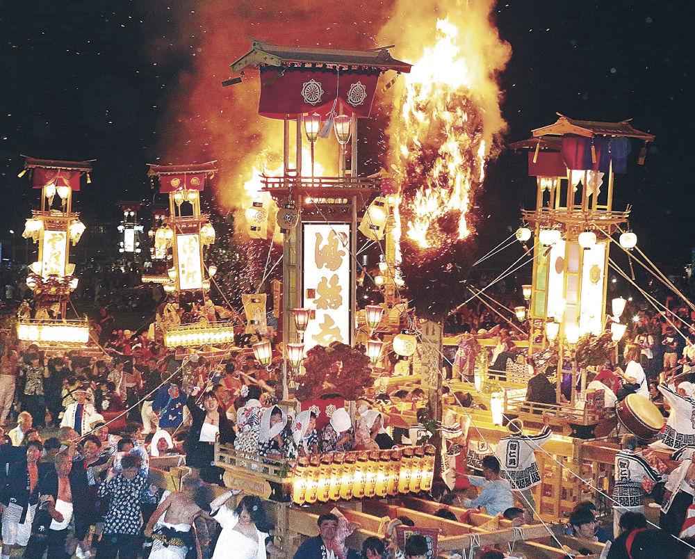 燃え盛る大たいまつのそばで乱舞するキリコ=能登町宇出津の宇出津港いやさか広場