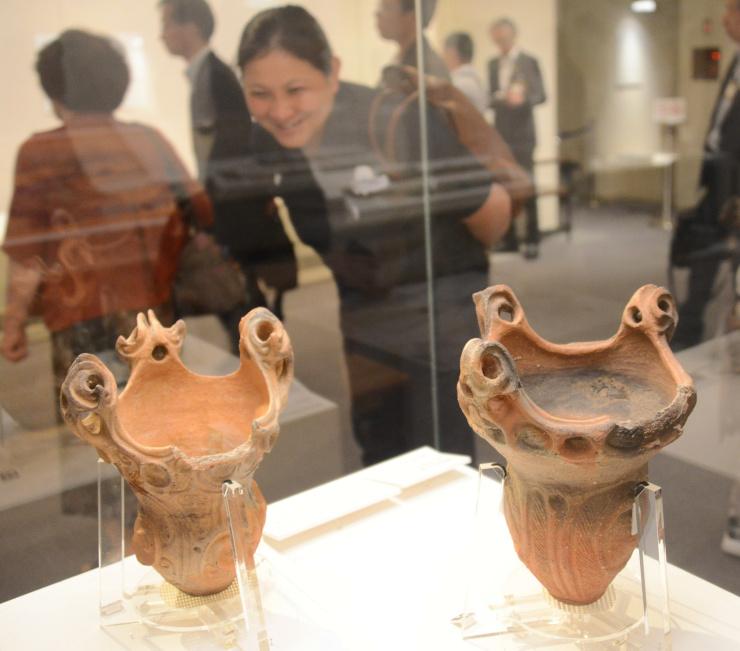 千曲市の遺跡で出土した縄文中期の土器(手前)などが並ぶ収蔵品展