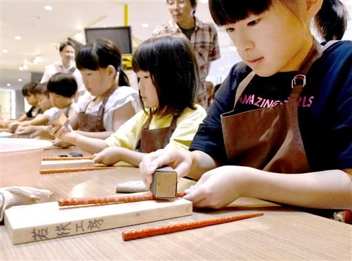若狭塗り箸の研ぎ作業を体験する児童たち=7月6日、福井県の小浜市食文化館