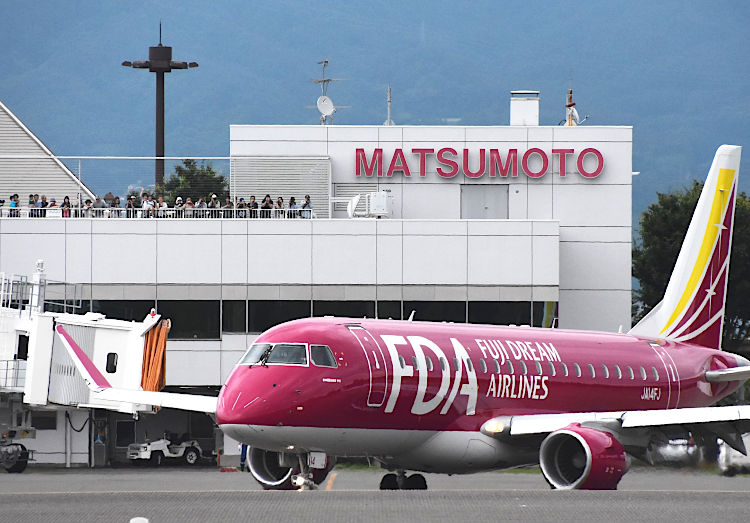 松本空港に飛来したワインレッド色のFDA機。送迎デッキには見物客らが詰め掛けた