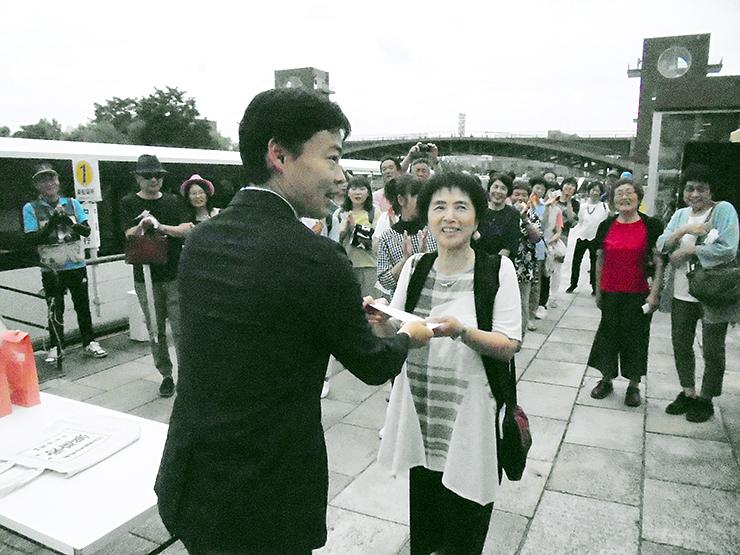 35万人目の乗船客として猪俣局長(左)から記念品を受け取る梅原さん