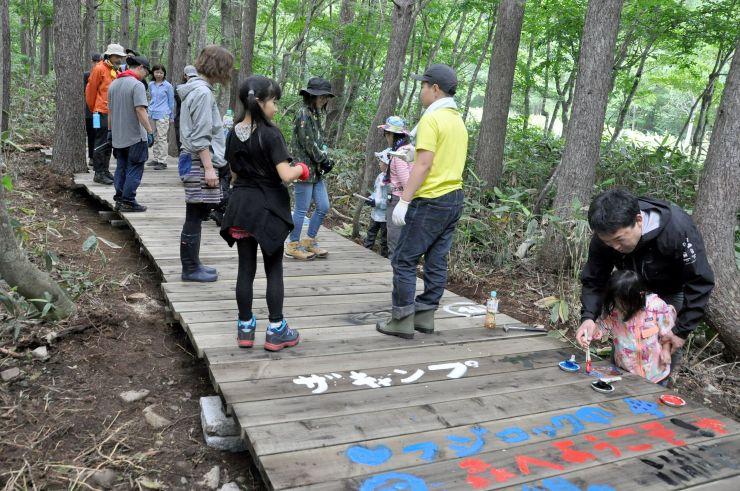 親子連れらが木道を整備した「ボードウォーク・ボランティアキャンプ」=6日、湯沢町三国