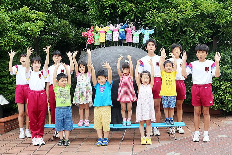 夏らしい華やかな浴衣に衣替えしたブロンズ像と、元気な歌声を響かせる子どもたち