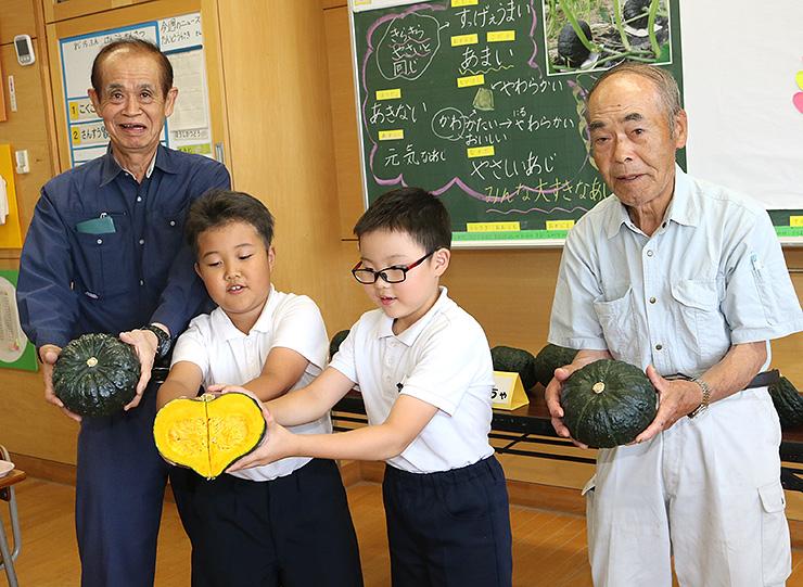 4分の1に切ったカボチャを二つ合わせてハート形をつくる児童。右は明和さん、左は喜田さん
