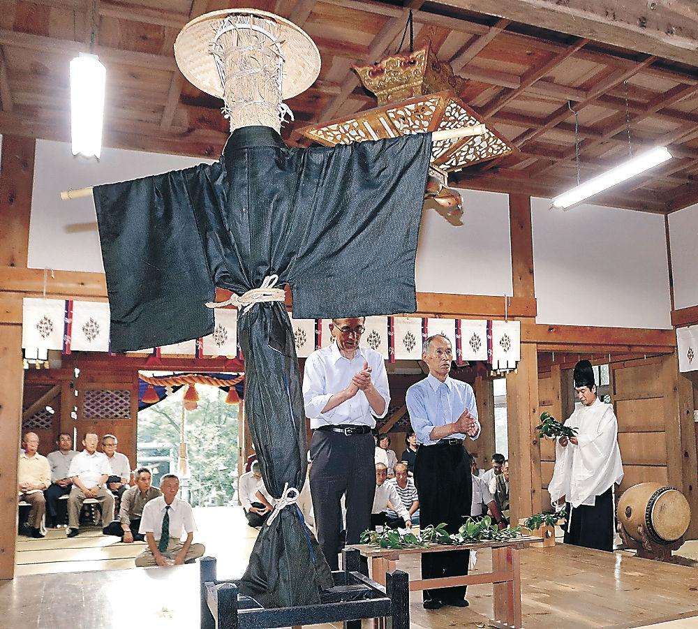 夏の例大祭で飾られたかかしを前に、玉串をささげる住民=今月5日、中能登町久江