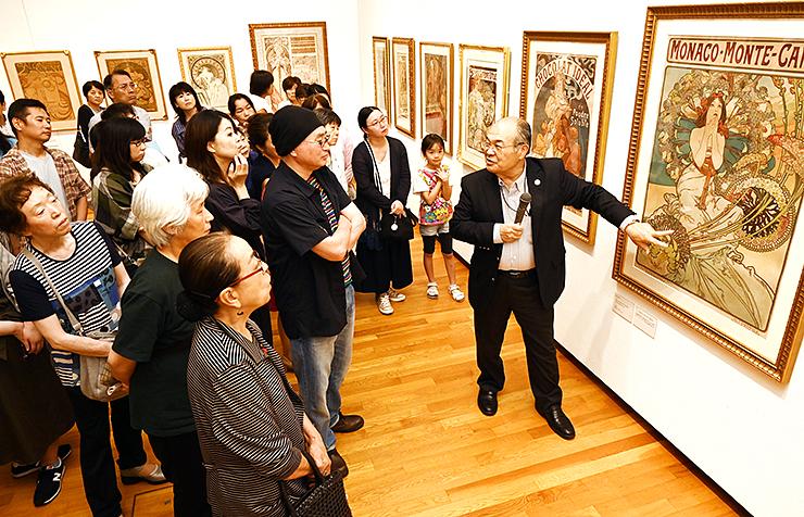 尾形さん(右)の解説を聞きながら熱心に鑑賞する大勢の来場者=高岡市美術館