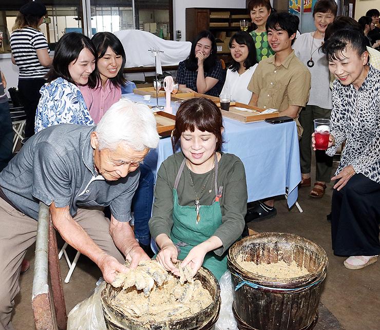 樽からこんか漬けを取り出す柿谷社長(手前左)と政希子さん