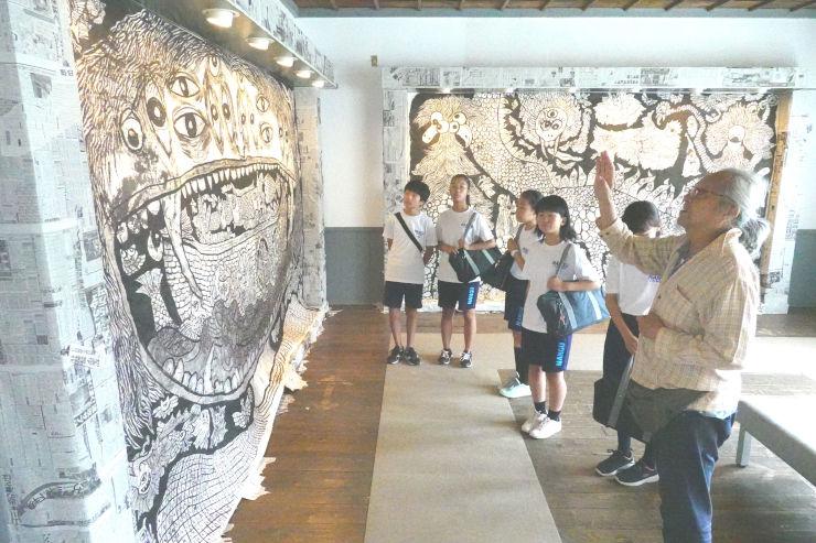 描いた妖怪について南宮中学校美術部の生徒に説明する上原さん(右)