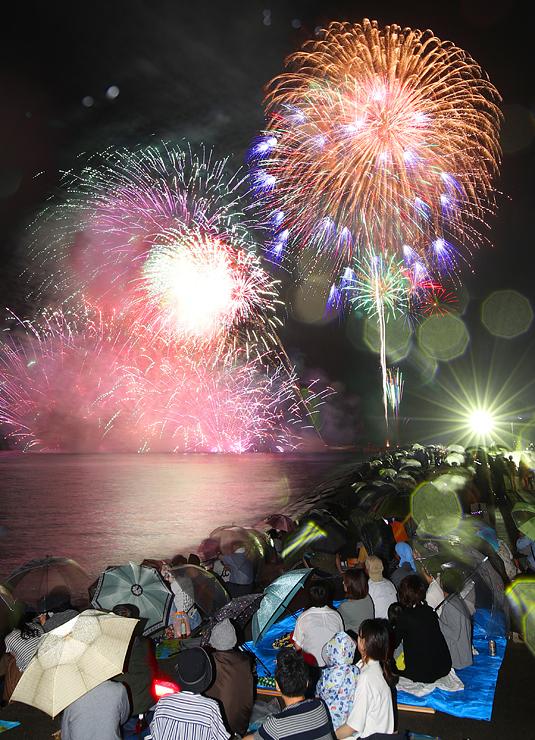 富山湾を照らす海空中スターマイン(左)と夜空を彩る光の大輪=滑川市の和田の浜(多重露光)