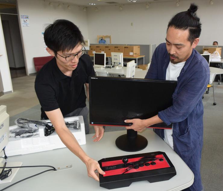 eスポーツで使うモニターやコントローラーを設置する田中さん(右)ら