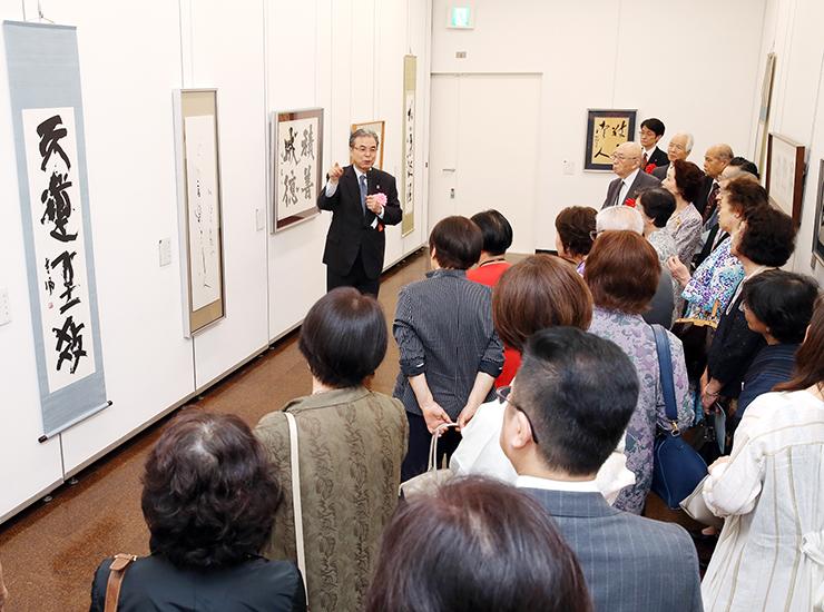 高木理事長(中央)の解説を聞きながら作品に見入る出席者=県民会館