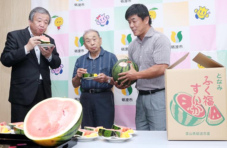 ふく福すいかを試食する夏野市長(左)や宮木組合長(中央)ら