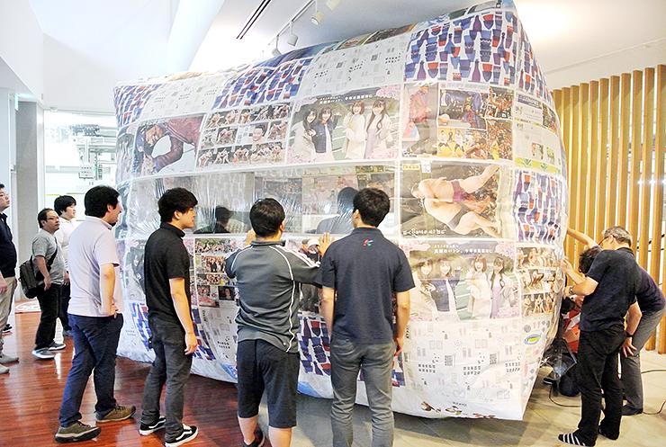 新聞で作った巨大エアドームの膨らみ具合を確かめるスタッフ
