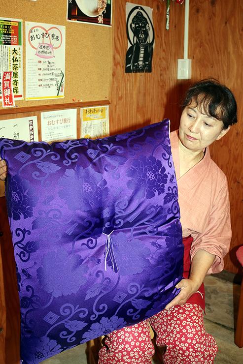 初開催の「おむすび寄席」のために寄贈された高座の座布団を手にする沢田店主