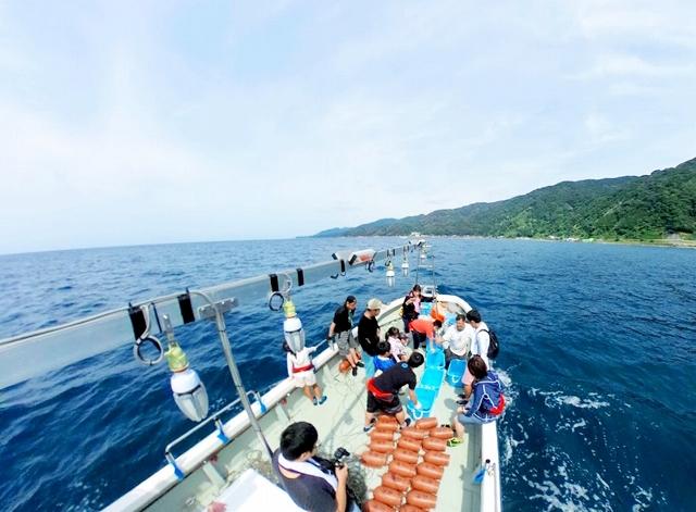 タコかご漁を楽しむ参加者たち=2018年、福井県福井市の茱崎漁港沖
