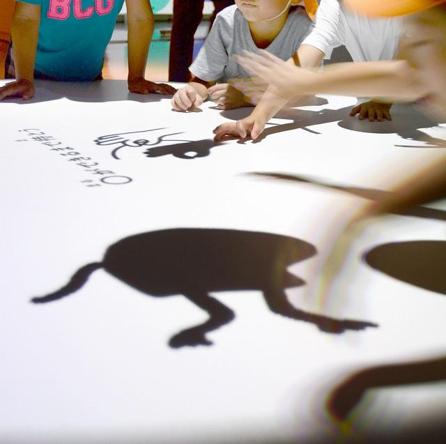 動きだす影絵を眺める園児たち=7月19日、福井県の福井市美術館