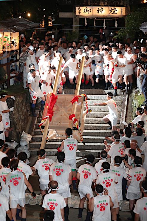 石段の上から豪快に放り投げられる「あばれみこし」=20日午後9時45分、宮田村の津島神社
